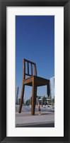 Framed Woman standing under a sculpture of large broken chair, Geneva, Switzerland