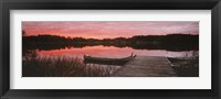 Framed Canoe tied to dock on a small lake at sunset, Sweden