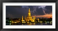 Framed Buddhist temple lit up at dawn, Wat Arun, Chao Phraya River, Bangkok, Thailand