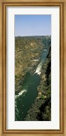 Framed Kayakers paddle down the Zambezi gorge away from the Victoria Falls, Zambia