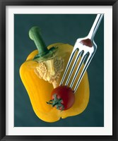 Framed Close up of half yellow pepper with cherry tomato in center on fork tines