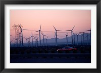 Framed Car moving on a road with wind turbines in background at dusk, Palm Springs, Riverside County, California, USA