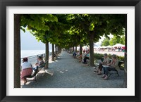 Framed People sitting on benches among trees at lakeshore, Lake Como, Cernobbio, Lombardy, Italy