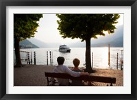 Framed Couple sitting on bench and watching ferry approaching dock along the Lake Como, Bellagio, Province of Como, Lombardy, Italy