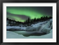 Framed wintery waterfall and aurora borealis over Tennevik River, Norway