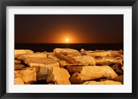 Framed moon rising behind rocks lit by a nearby fire in Miramar, Argentina