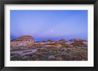 Framed Gibbous moon and crepuscular rays over Dinosaur Provincial Park, Canada