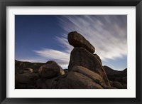 Framed Large boulders backdropped by stars and clouds, California