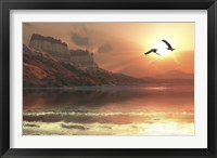 Framed Two Bald Eagles fly along a mountainous coastline at sunset