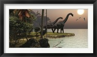 Two Brachiosaurus dinosaurs enjoy a beautiful sunset Framed Print