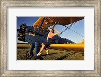 Framed 1940's style pin-up girl sitting on the wing of a Stearman biplane