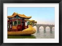 Framed Summer Palace, a traditional Dragon Boat passes the Seventeen Arch Bridge, Kunming lake, Beijing, China