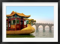 Framed Summer Palace, a traditional Dragon Boat passes the Seventeen Arch Bridge, Kunming lake, Beijing, China