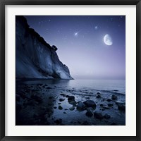 Framed Rising moon over ocean and mountains against starry sky
