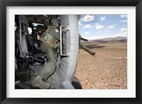 Framed HH-60G Pave Hawk gunner fires his GAU-17 machine gun
