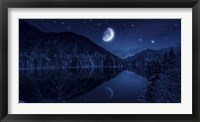 Framed Moon rising over tranquil lake in the misty mountains against starry sky