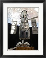Framed Space Shuttle Atlantis' arm lifts the Hubble Space Telescope from the cargo bay