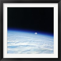 Framed Outer space shot of storm system in early stage of formation with moon in background