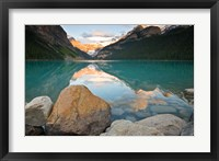 Framed Rocky Mountains and boulders reflected in Lake Louise, Banff National Park, Alberta, Canada