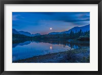 Framed Crescent moon over Middle Lake in Bow Valley, Alberta, Canada