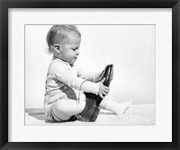 Framed 1960s Baby Boy Trying To Put On Man'S Shoe